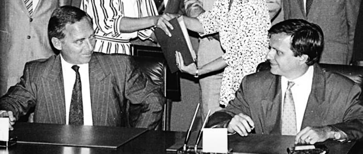 3.8.1990, Berlin, während die beiden Exemplare des deutsch-deutschen Wahlvertrages für die zweite Unterschrift ausgetauscht werden (Hintergrund), freuen sich die Unterhändler, DDR-Staatssekretär Günther Krause (r.) und BRD-Innenminister Wolfgang Schäuble. (Foto: Bundesarchiv, Bild 183-1990-0803-016 / Settnik, Bernd / CC-BY-SA 3.0)