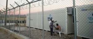 Flüchtlinge im Lager auf Chios, Griechenland (Foto: [Url=https://commons.wikimedia.org/wiki/File:Inhabitants_of_Suda_refugee_camp_seen_through_barbed_wire_fence_surrounding_it,_Chios,_Grece,_Aegean_Sea._29_September,_2016.jpg]Mstyslav Chernov/Wikimedia Commons[/url])