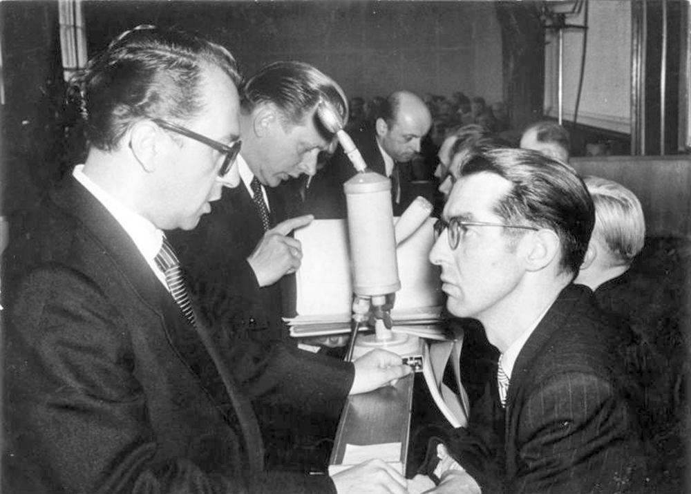 """1955, Prozess gegen fünf Agenten der berüchtigten Westberliner Diversanten- und Spionagezentrale """"Kampfgruppe gegen Unmenschlichkeit"""". Der Verteidiger (links) im Gespräch mit dem Angeklagten Gerhard Benkowitz."""