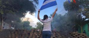 Bilder, wie wir sie vom letzten Jahr aus Venezuela kennen: Eine Frau posiert mit Fahne vor brennenden Barrikaden. (Foto: Voice of America)