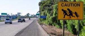 Kurz hinter der Grenze bei Tijuana warnt ein Schild Autofahrer vor Flüchtlingsfamilien, die die Fahrbahn überqueren könnten – sie sollen nun vom Militär aufgehalten werden. (Foto: Jonathan McIntosh)