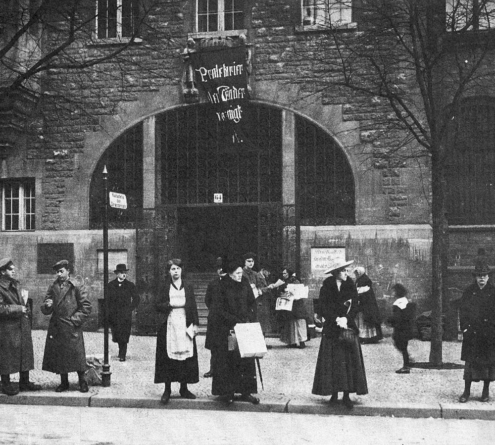 """Vor dem Neuköllner Rathaus: Warten auf die Straßenbahn, linke und weniger linke Zeitungen zum Mitnehmen, über dem Tor die Fahne: """"Proletarier aller Länder …"""""""