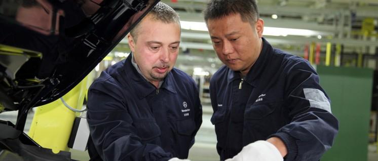 Zwei Arbeiter von Beijing Benz Automotive (BBAC) m neuen Kompaktwagen-Werk in Peking, China. BBAC ist ein Joint Venture-Unternehmen, das ursprünglich von American Motors (AMC) und Beijing Automotive Industry Holding Corporation gegründet wurde. (Foto: 2016 Daimler AG)