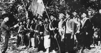 Vo Nguyen Giap (links), der spätere Oberbefehlshaber der Volksarmee, und vietnamesische Kämpfer der Vietminh Im Dschungel nahe Kao Bak Lang, 1944 (veröffentlicht in: Jean Chesneaux: Geschichte Vietnams. Rütten& Loening, Berlin 1963)