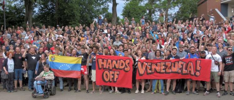 Fäuste ballen, Hände weg: Nach der Rede Carolus Wimmers, Internationaler Sekretär der Kommunistischen Partei Venezuelas, zeigten die Teilnehmer mit diesem Foto ihre Solidarität mit dem venezolanischen Volk, das sich gegen Angriffe aus den USA verteidigt.  (Foto: Tom Brenner)