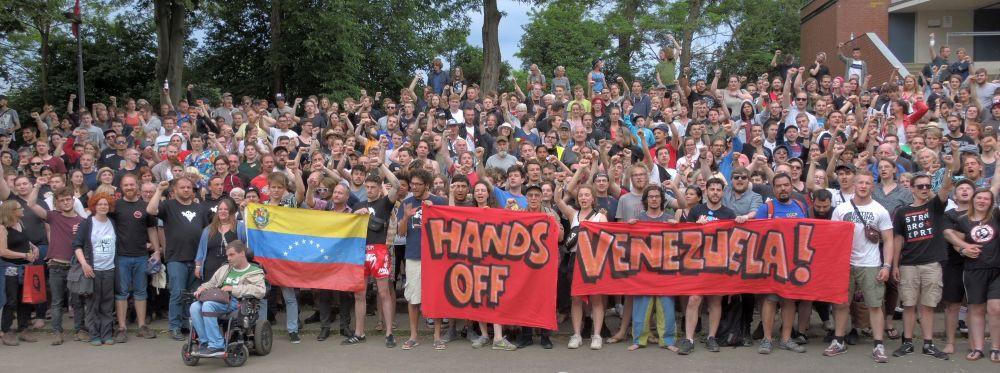 Fäuste ballen, Hände weg: Nach der Rede Carolus Wimmers, Internationaler Sekretär der Kommunistischen Partei Venezuelas, zeigten die Teilnehmer mit diesem Foto ihre Solidarität mit dem venezolanischen Volk, das sich gegen Angriffe aus den USA verteidigt.