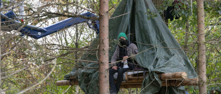 Oben bleiben: Umweltschützer im Baumhaus am Freitag vergangener Woche, im Hintergrund das Gerät, mit dem die Polizei den Wald für RWE räumt. (Foto: Hubert Perschke/r-mediabase.eu)