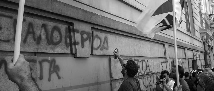 Besuch beim Unternehmerverband – PAME-Aktivist besprüht die Fassade. (Foto: PAME)