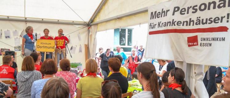 Grüße an die Streikenden: Am Donnerstag vergangener Woche halten VertreterInnen von Betrieben und Organisationen Grußworte im Streikzelt vor der Essener Uniklinik– hier von einem Dortmunder Krankenhaus. (Foto: Dave Kittel)