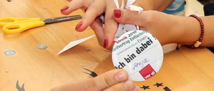 Sie sind dabei. Im Streikzelt vor der Essener Uniklinik stellen Kolleginnen Buttons her. (Foto: Peter Köster)
