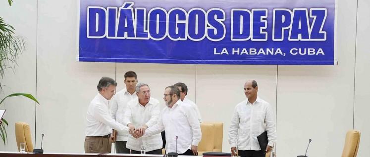 Kuba ist Vermittler in den Friedensverhandlungen – und Bezugspunkt für eine neue Gesellschaft: Raúl Castro beim Handschlag zwischen dem kolumbianischen Präsidenten Santos und Timoleón Jiménez, dem Oberkommandierenden der FARC. (Foto: Yenny Muñoa / CubaMINREX)