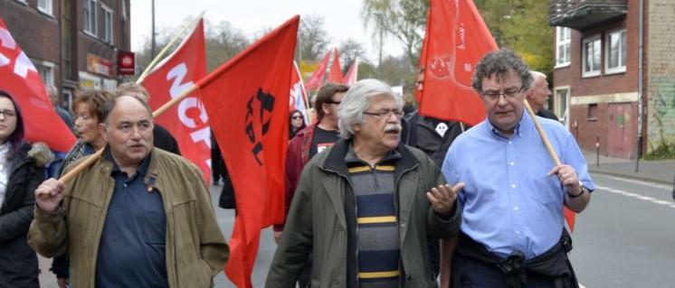 Patrik Köbele (ganz rechts) im Gespräch mit Ali Ruckert (KPL) auf der Demo vor der Vier-Parteien-Konferenz in Münster 2017 (Foto: Tom Brenner)