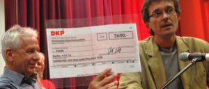 Das Ergebnis der Spendenaktion der DKP, 3 600 Euro, wurde Dimos Koubouris (l.), Mitglied des Exekutivkomitees der PAME auf der Veranstaltung überreicht. (Foto: Tom Brenner)