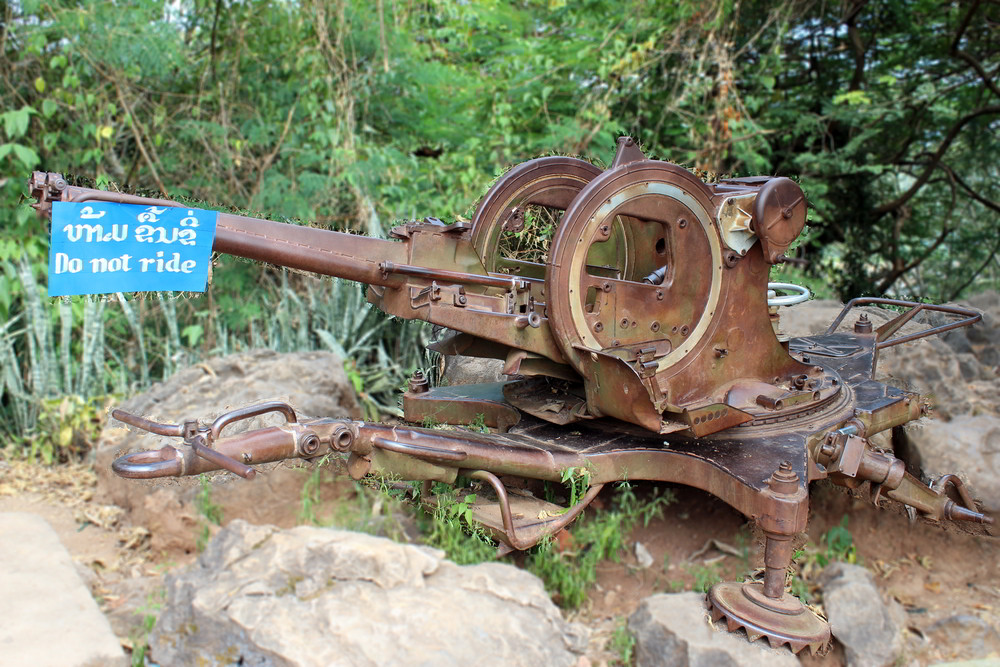 Eine verrostete Maschinenkanone erinnert an den Luftkrieg der USA gegen Laos.