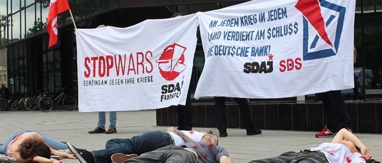 """""""An jedem Krieg in jedem Land verdient am Schluss die Deutsche Bank"""": SDAJ-Mitglieder bei einer """"Outing-Aktion"""" vor der Zentrale der Deutschen Bank in Frankfurt. (Foto: SDAJ)"""