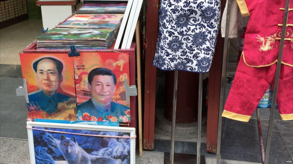 Je nach Blickrichtung: Mal ist Mao zu sehen, mal Xi. Hologramm an einem Marktstand in der VR China.
