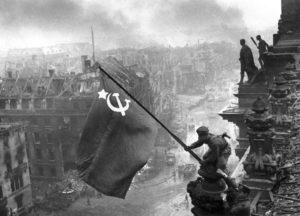 Soldat der Roten Armee hisst Sowjetflagge auf dem Reichstagsgebäude.